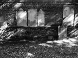 Broken headstones along back wall of Colonial